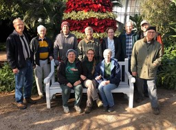 A group picture of Tiffany's Group in the Conservatory in front of the Poinsettia tree